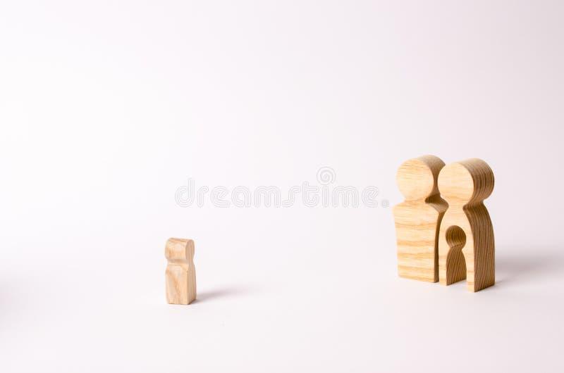 父母木小雕象看一个孤独的孩子 一个孤儿孩子正在寻找一个家庭 一对贫瘠夫妇采取被放弃的孩子 免版税库存图片