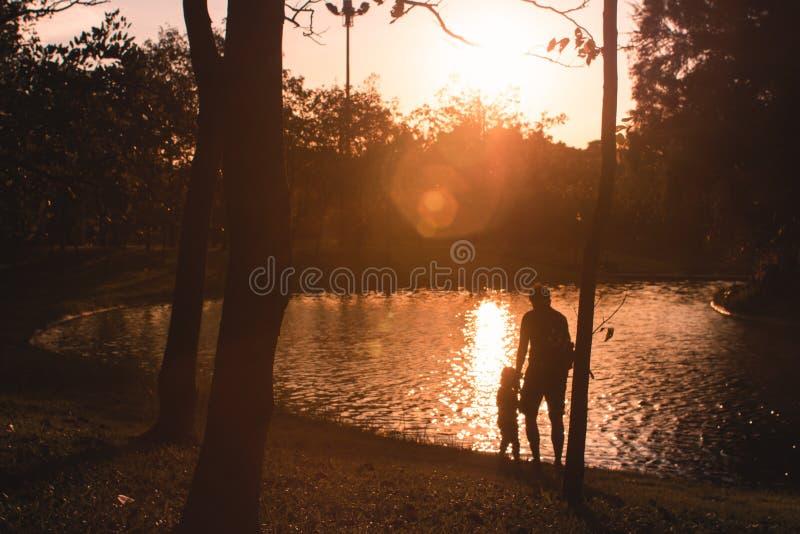 父母爸爸和女儿在美好的日落自然户外背景的儿童剪影家庭  库存图片