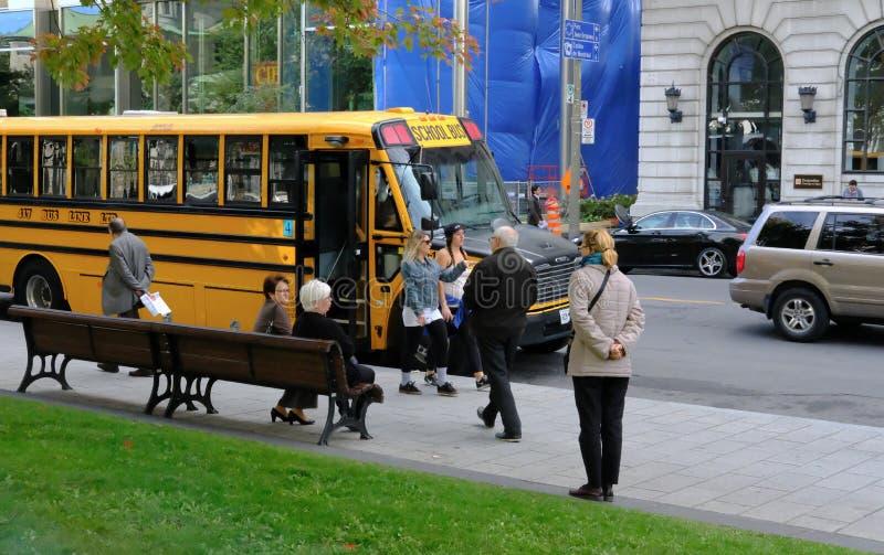 父母看等待校车到孩子下落从学校的 免版税库存图片