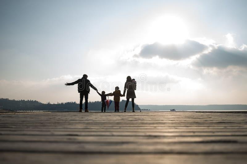 父母背面图有握手的孩子的 免版税库存图片