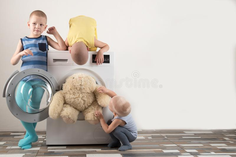 父母被买一台新的洗衣机 孩子设法打开它和洗涤软的玩具 愉快的男孩在家使用 库存照片