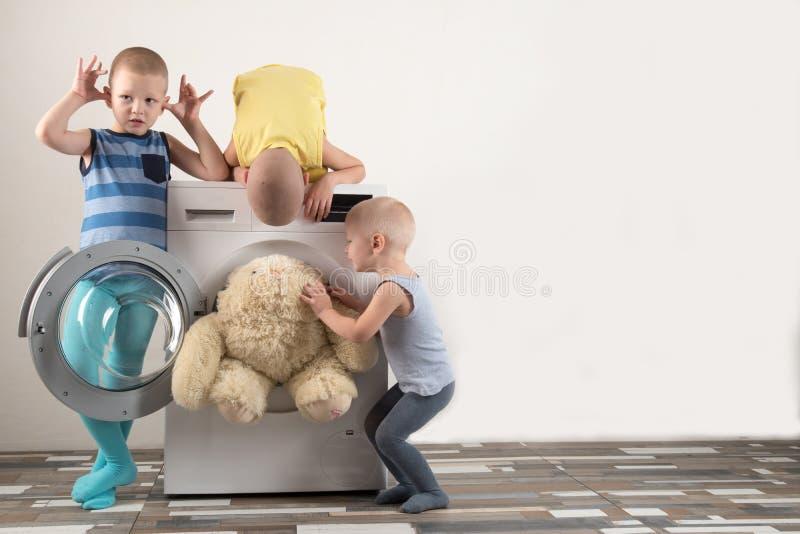 父母被买一台新的洗衣机 孩子设法打开它和洗涤软的玩具 愉快的男孩在家使用 免版税库存照片