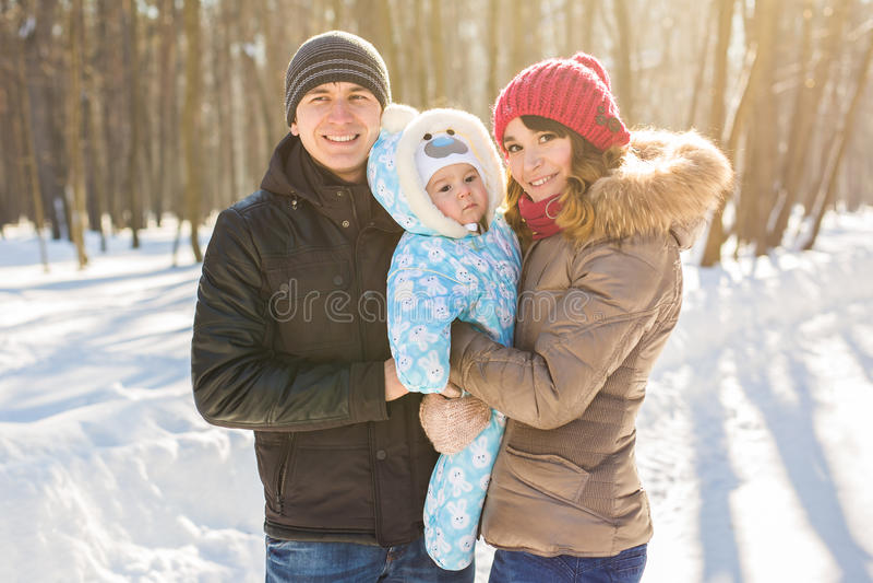 父母身分、时尚、季节和人概念-与婴孩的愉快的家庭在冬天穿衣户外 库存照片