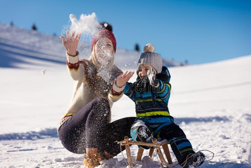 父母身分、时尚、季节和人概念-有雪撬的走在冬天的孩子的愉快的家庭户外 免版税图库摄影
