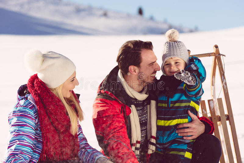 父母身分、时尚、季节和人概念-有雪撬的走在冬天的孩子的愉快的家庭户外 库存照片