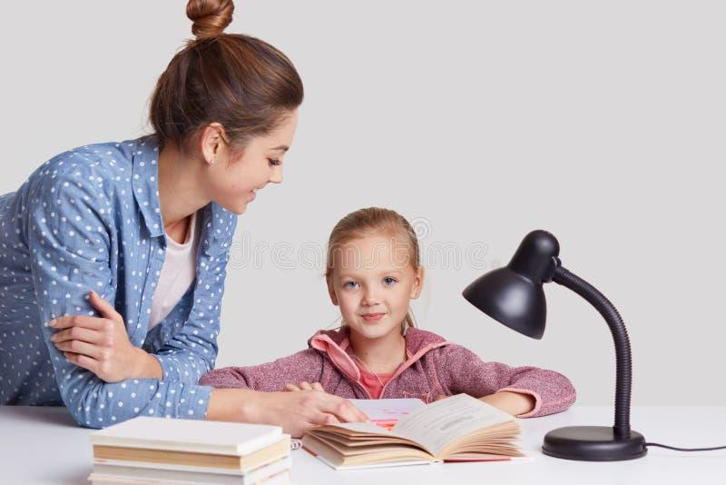 父母身分,学习和教育概念,可爱的蓝眼睛的女孩在工作场所坐,与母亲一起读书, 免版税库存照片