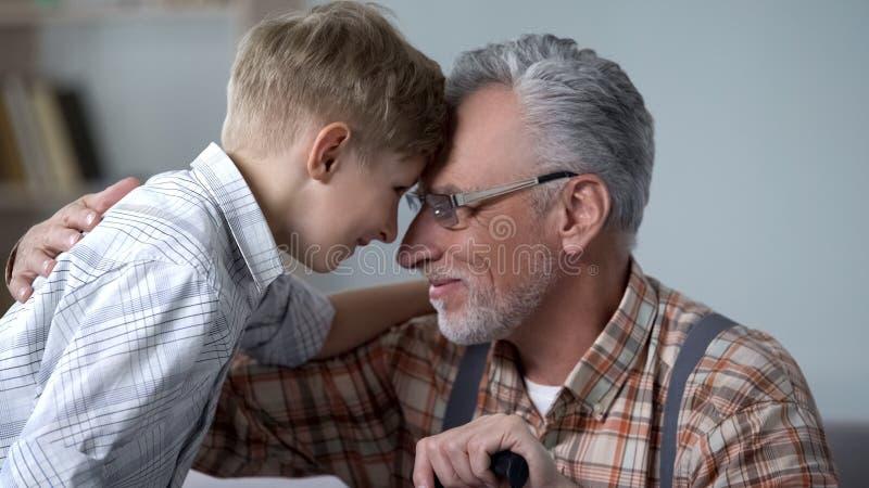 爷爷和男孩倾斜的前额一起,参观周末,家庭爱 免版税库存照片