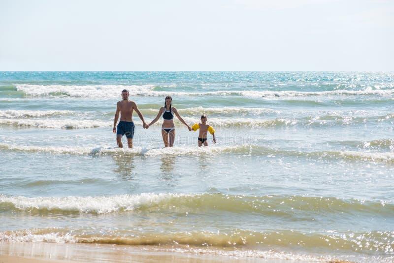 爸爸、妈妈和儿子在游泳以后从海出来 Bif风暴波浪 男孩iin浮水圈 免版税库存照片