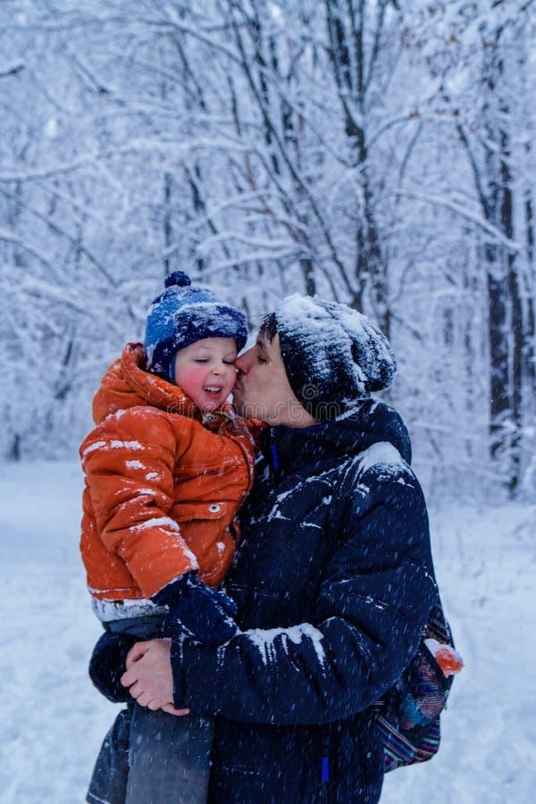 爸爸亲吻他的儿子外面,背景的冬天森林,下雪,愉快和快乐 免版税库存照片