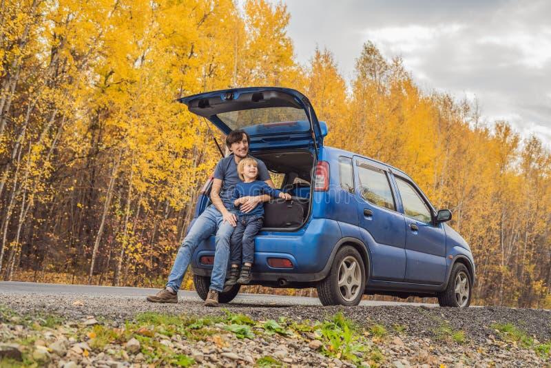 爸爸和儿子休息在旅行的路一边 与儿童概念的旅行 免版税库存图片