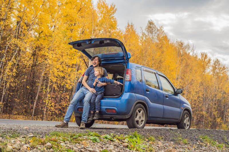 爸爸和儿子休息在旅行的路一边 与儿童概念的旅行 库存图片