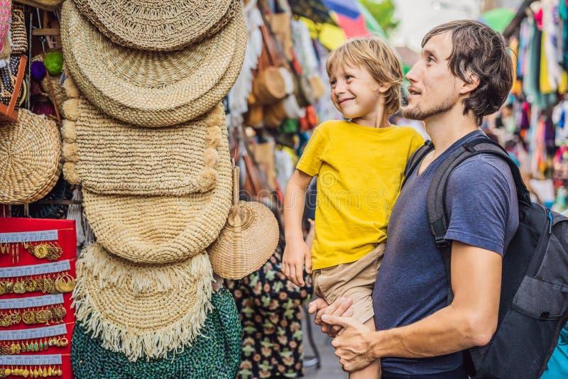 爸爸和儿子在一个市场上在Ubud,巴厘岛 卖巴厘岛的纪念品和工艺品典型的纪念品店在著名 库存照片