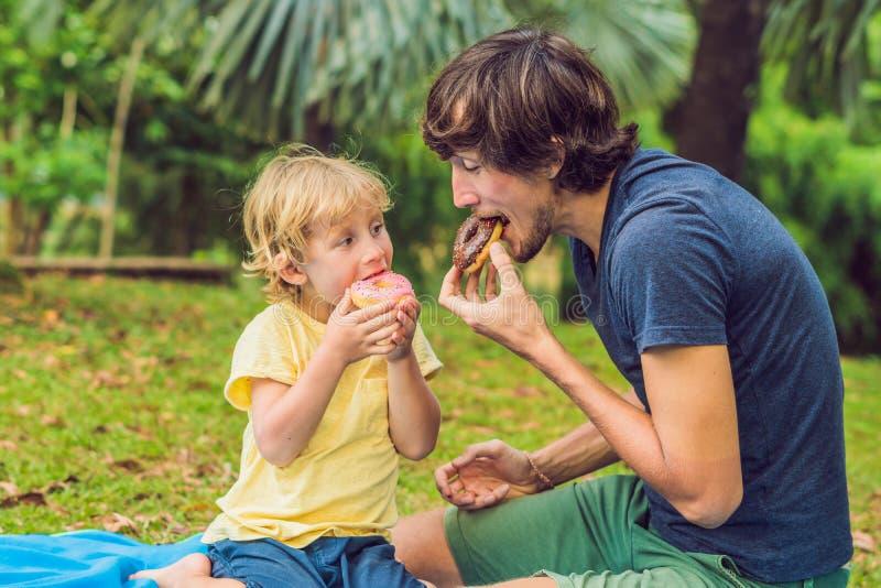 爸爸和儿子在公园吃着一个多福饼 在家庭的有害的营养 免版税库存图片
