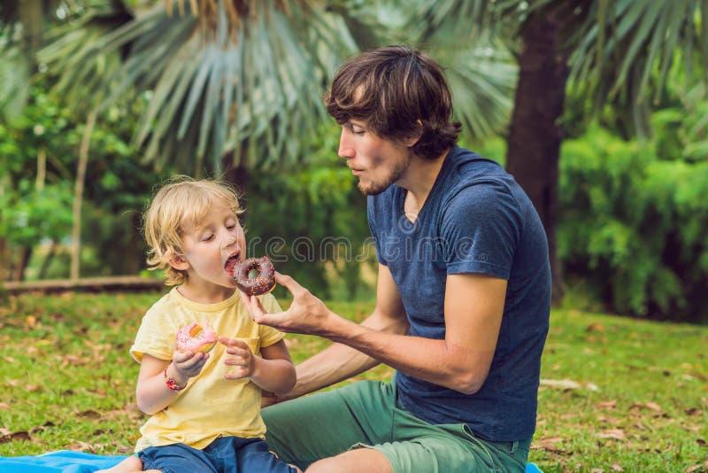 爸爸和儿子在公园吃着一个多福饼 在家庭的有害的营养 免版税图库摄影