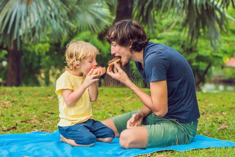 爸爸和儿子在公园吃着一个多福饼 在家庭的有害的营养 库存照片