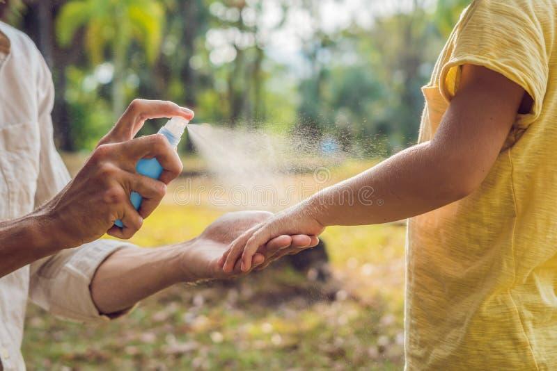 爸爸和儿子用途蚊子浪花 在皮肤的喷洒的杀虫剂 免版税库存照片