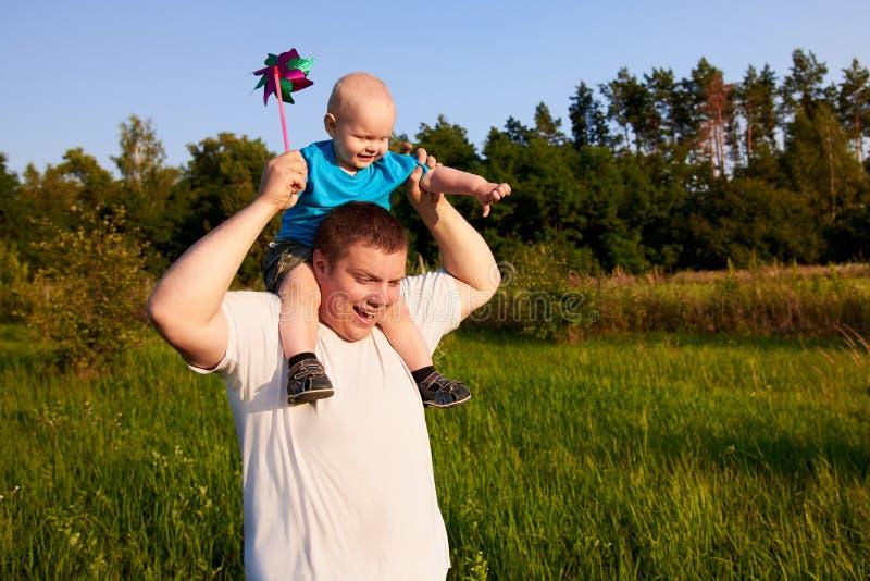 爸爸和儿子获得乐趣本质上在夏天,抱他的他的肩膀的父亲孩子与轮转焰火 免版税库存照片