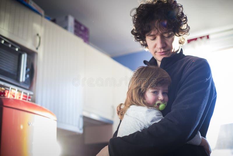 爸爸和在家拥抱的女婴 免版税图库摄影
