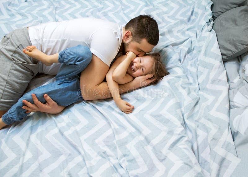 爸爸和女儿在家获得乐趣在床上 日父亲s 免版税库存图片