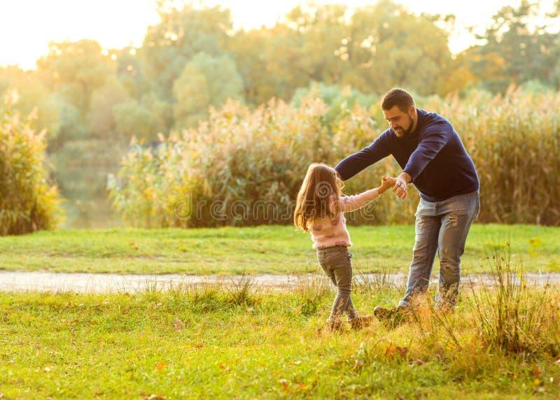 爸爸和女儿在秋天停放戏剧笑 免版税图库摄影