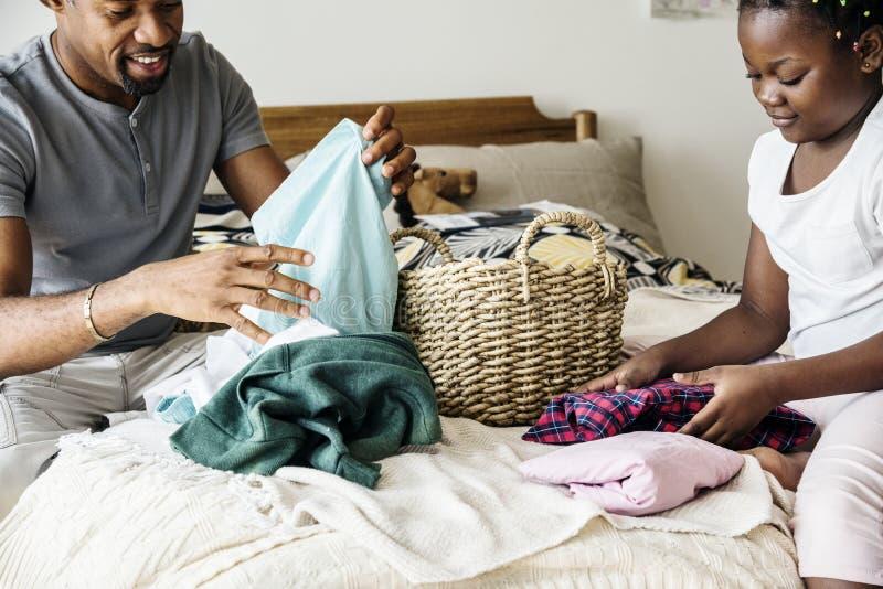 爸爸和女儿折叠的衣裳在卧室一起 免版税库存照片