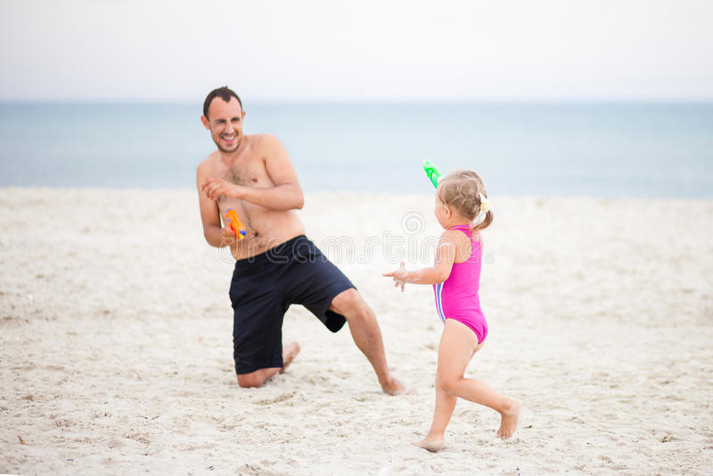 爸爸和女儿演奏在海的水枪 免版税库存图片