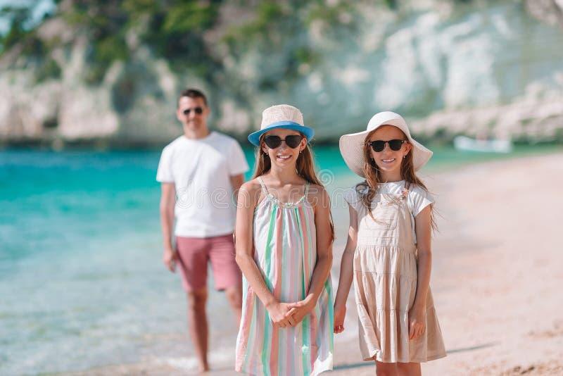 爸爸和孩子愉快的美丽的家庭在白色海滩 免版税库存图片
