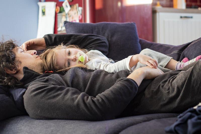 爸爸和放松在沙发的女婴 免版税库存图片