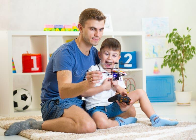 爸爸和他的儿子儿童游戏与RC直升机戏弄 库存图片
