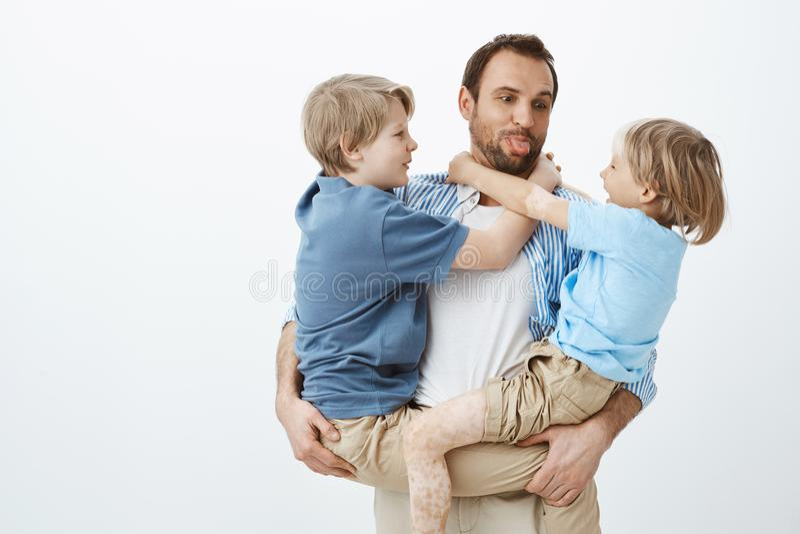 爸爸喜爱花费与家庭的时间 拿着胳膊的儿子和伸出舌头的无忧无虑的愉快的父亲,做面孔 免版税库存图片