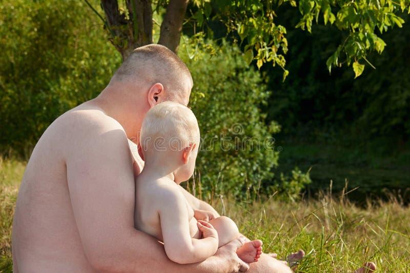爸爸在一个热的夏日拥抱他的河的河岸的一点儿子 o 图库摄影