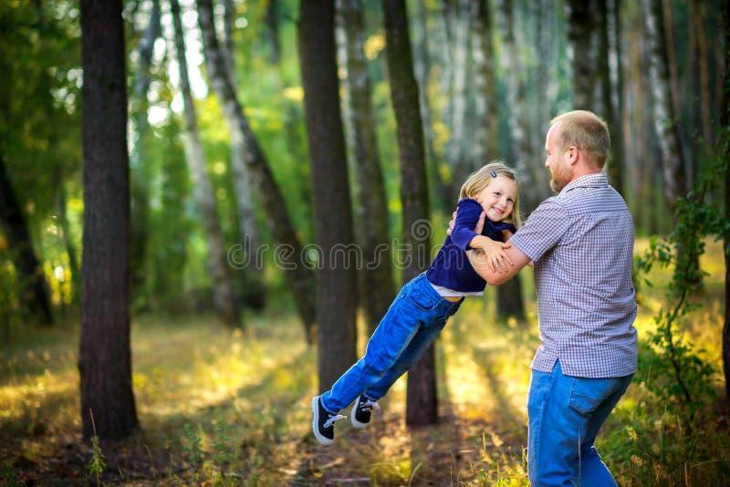 爸爸在有他心爱的女儿的公园在他的手上走在日落,投掷  免版税库存图片