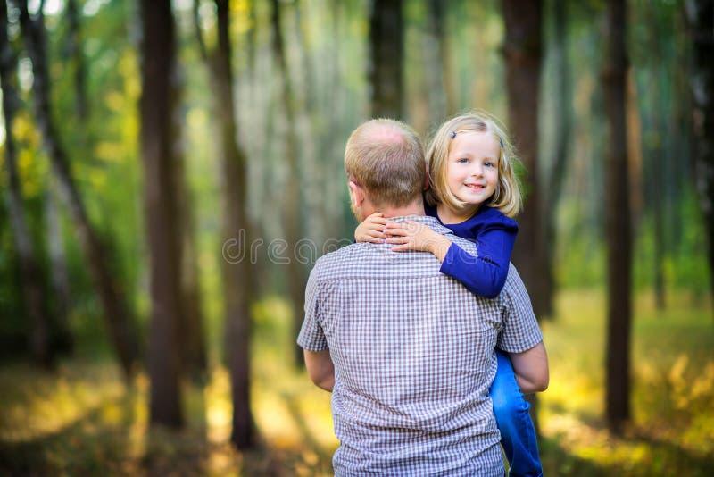 爸爸在有他心爱的女儿的公园走在日落 免版税库存图片