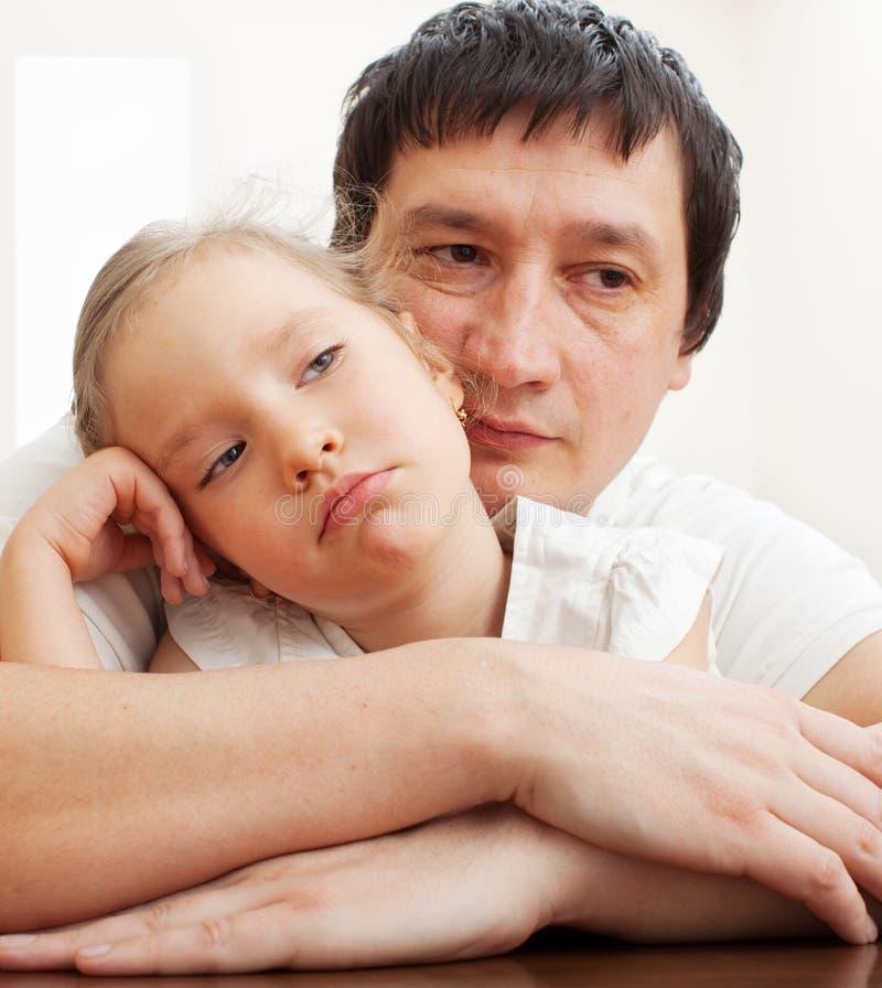 爸爸安慰一个哀伤的女孩 库存图片