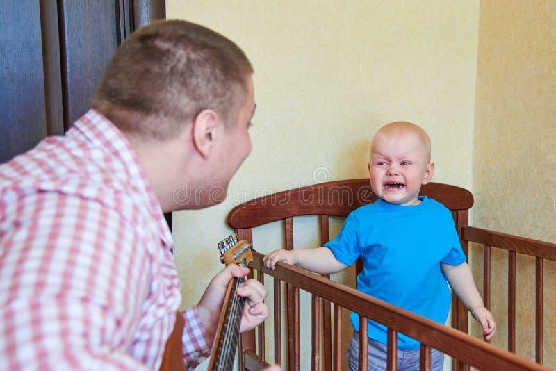 爸爸弹吉他慰问他哭泣的儿子 库存图片