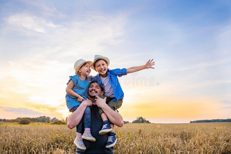 爸爸抱他的胳膊的两个孩子 使用在平衡的日落的领域的幸福家庭 免版税库存照片