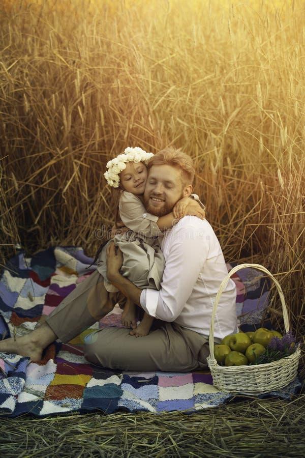 爸爸拥抱麦田的女儿 免版税库存照片