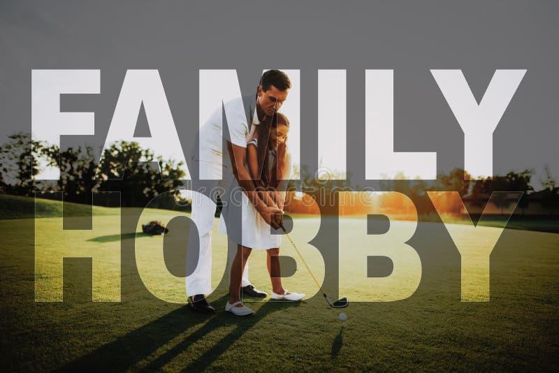 爸爸教孩子采取射击打高尔夫球的家庭爱好 图库摄影