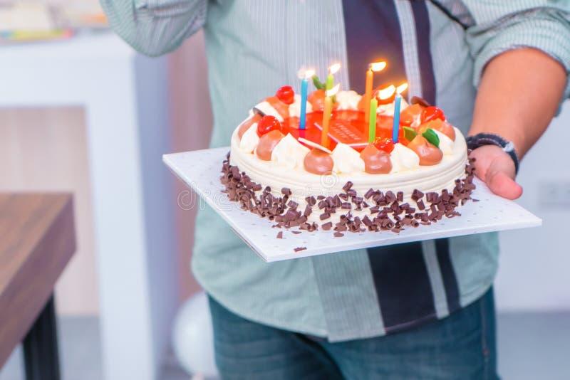 爸爸照明设备在生日蛋糕的生日蜡烛孩子的 库存图片