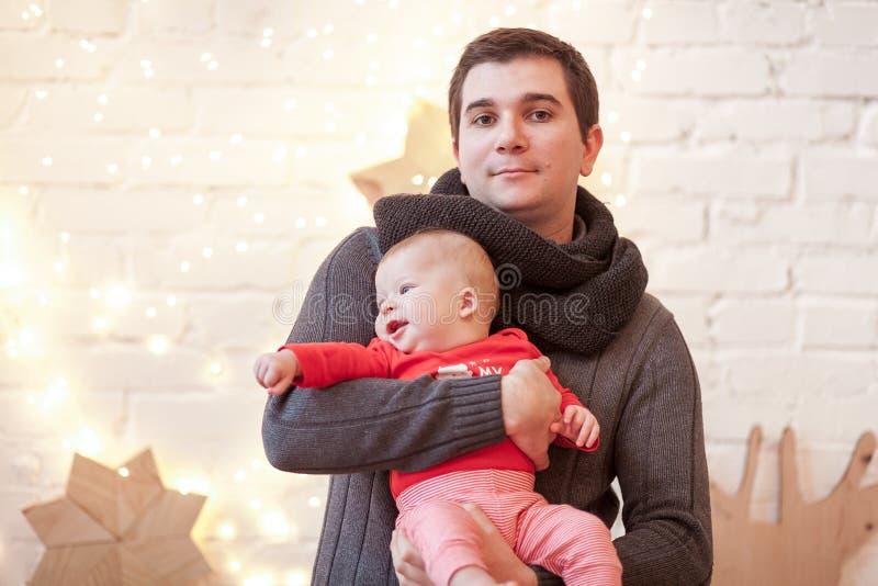 爸爸穿被编织的毛线衣,并且围巾在他的手上拿着站立在一间明亮的屋子的红色T恤杉的一个小儿子反对a 免版税库存照片