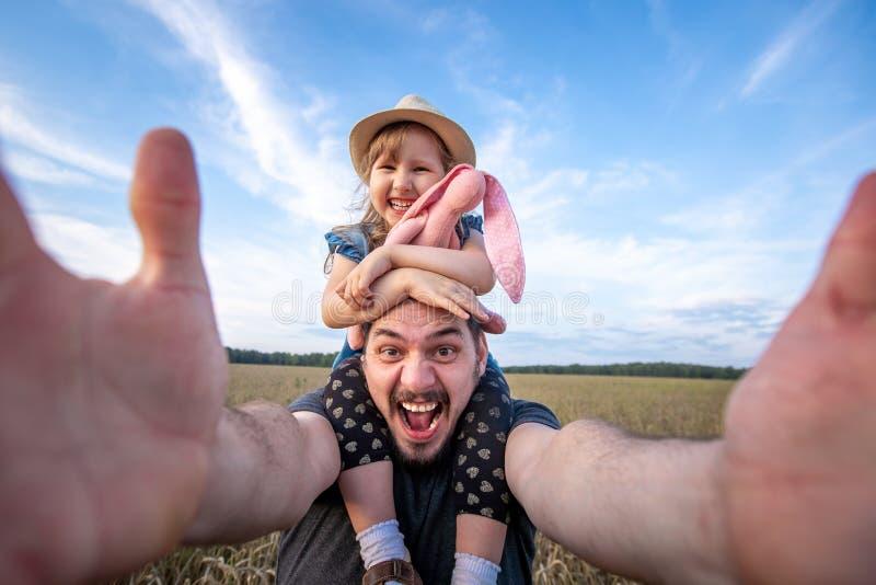 爸爸继续他的女儿坐他的肩膀 快乐的父亲和女儿采取selfies在胳膊的长度照相机 通过看得 免版税库存图片