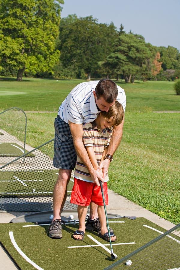 爸爸高尔夫球儿子教学 库存图片
