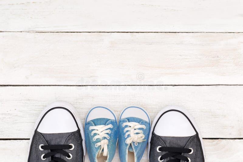 爸爸` s起动和婴孩` s运动鞋,在白色木背景, f 免版税库存图片