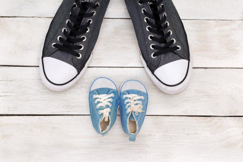 爸爸` s起动和婴孩` s鞋子,父亲节概念 库存图片