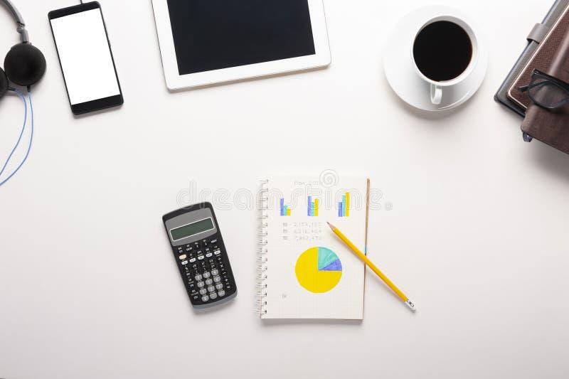 片剂、智能手机、计算器、笔记本和一杯咖啡顶视图在白色背景的 库存照片
