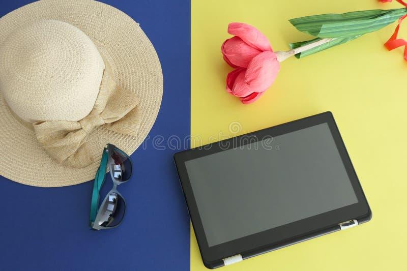 片剂、秸杆海滩女性帽子有弓的,太阳镜和纸手工制造花,隔绝在黄色和蓝色背景 免版税库存照片