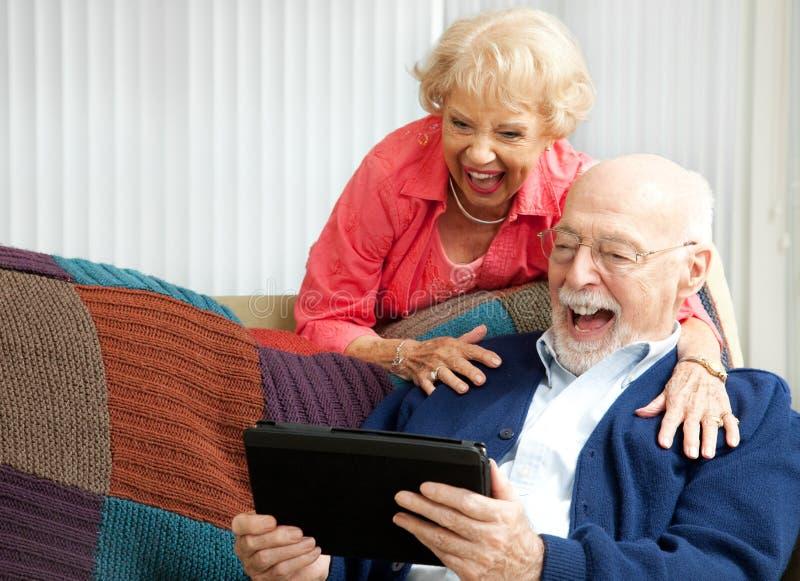 片剂个人计算机-高级夫妇笑 库存图片