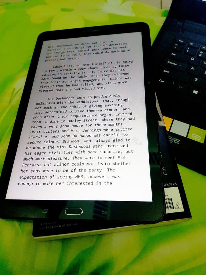 片剂书和膝上型计算机,当工作时 免版税库存图片