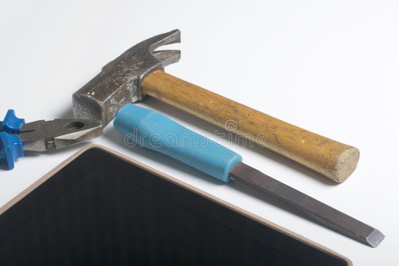 片剂和工具 桌的白色表面上是片剂、丝球、凿子和钳子 破坏和修理选举 免版税库存图片