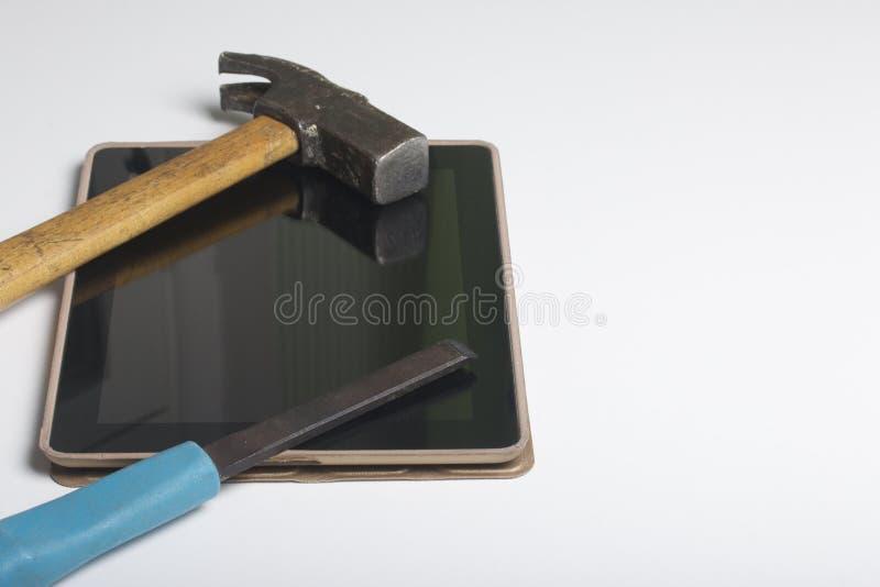 片剂和工具 桌的白色表面上是片剂、丝球、凿子和钳子 破坏和修理选举 库存照片